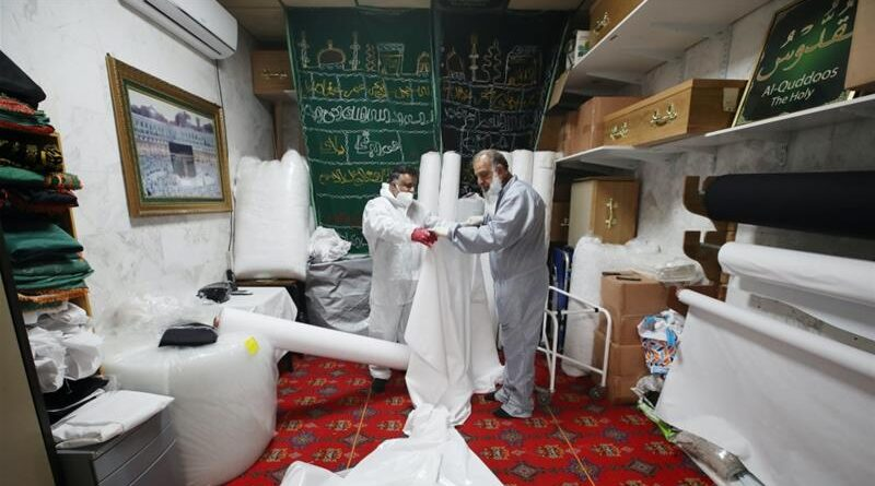 Workers prepare shrouds to wrap bodies in the Central Jamia Mosque Ghamkol Sharif, which is currently being used as a temporary morgue in Birmingham, UK, April 21, 2020 [Carl Recine/Reuters]